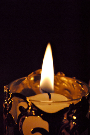 votive candle: A single white votive candle in a golden holder.
