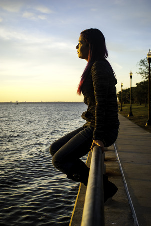 Young woman sitting on a handrail by the ocean.