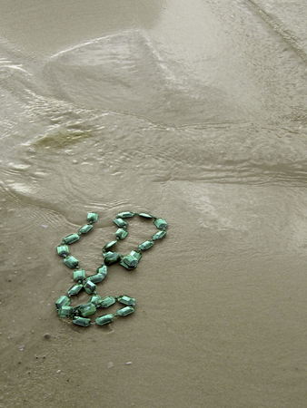 aftermath: The aftermath; broken Mardi Gras beads on the beach.