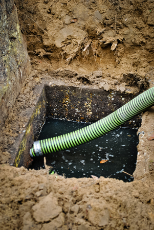 septic tank: Suction hose ready to drain the septic tank Stock Photo