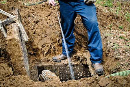 Power wash to rinse the septic tank walls Stock Photo