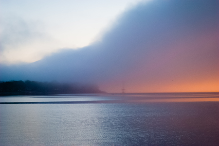 Foggy sunrise over the water of the bay Stock Photo
