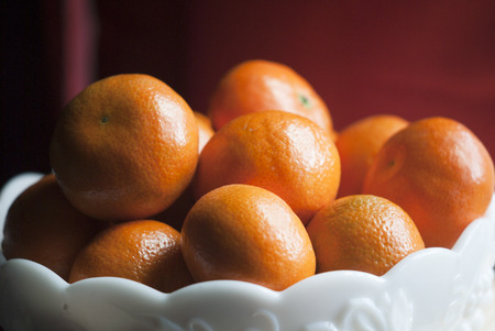 clementines: Clementives in a milk-glass bowl.