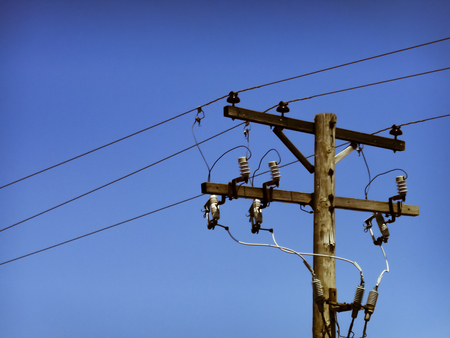 Utility pole with electric wires against blue sky