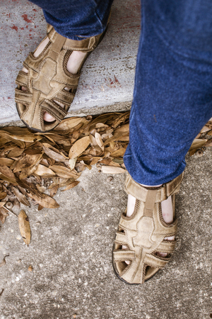 Womans feet in sandals stepping forth. Stock Photo