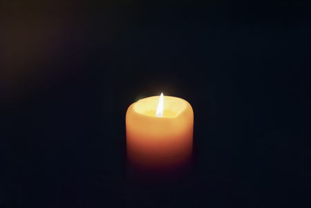 White candle shining in the dark