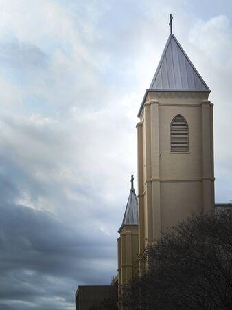 Church steeple rises high through stormy skies.