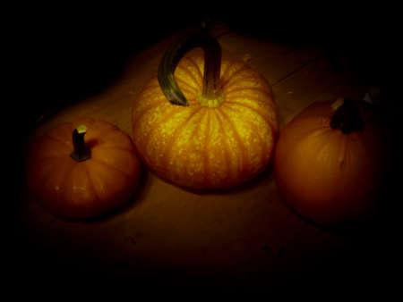 Three pumpkins in a dark, moody scene for Halloween or autumn Stock Photo
