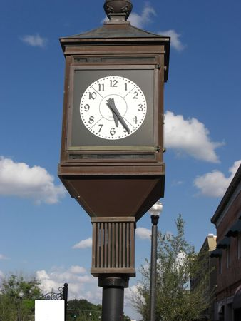 A large clock is on the side of a road in a town. 版權商用圖片