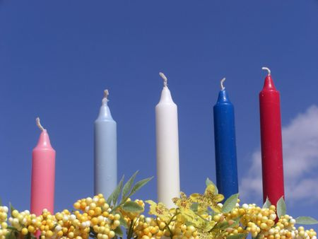 A set of five colorful candles are within a bunch of flowers, and are standing against a blue sky. 版權商用圖片