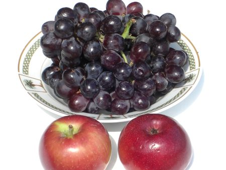 A bowl of nutritious grapes and two red apples on the side. Фото со стока