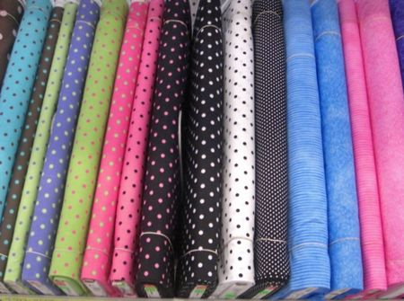 fabric textures: Rolls of fabric in different colors, textures and designs are neatly packed on a shelf in a retail store.