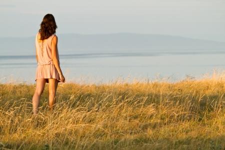 giovane donna in abito guarda al mare