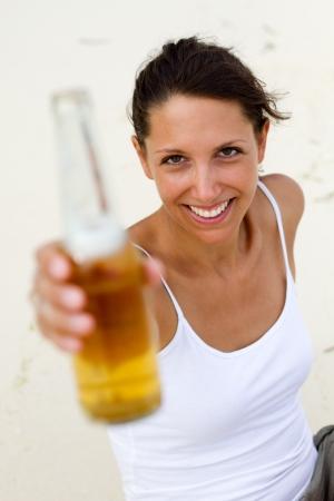 donna con la birra sulla spiaggia Archivio Fotografico