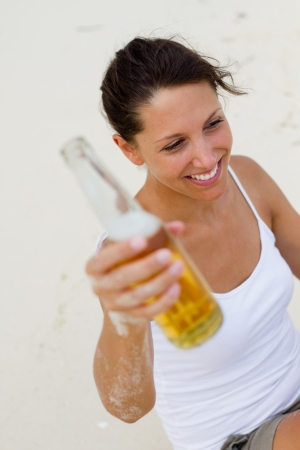 woman with beer on beach Stock Photo