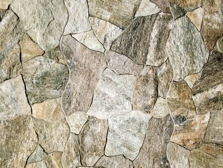 Texture - Stone wall made with man-made stone tiles in multiple colors providing a rustic look for indoor or outdoor environments.