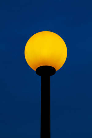 in the foreground a street light, near a park photo