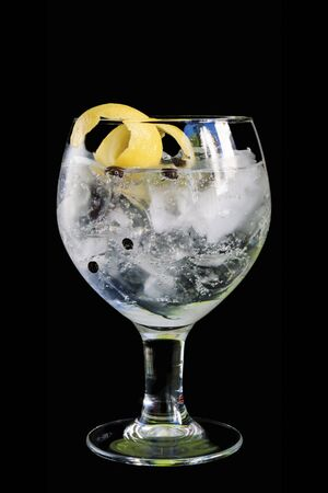 Gin and Tonic in a glass balloon isolated on black Фото со стока