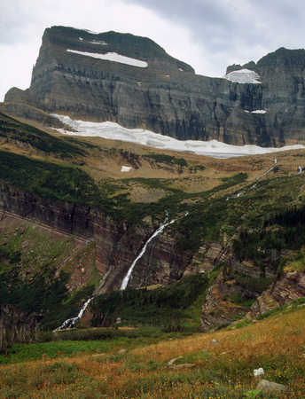 Mount Gould and waterfall along the Grinnell Glacier Trail, Glacier National Park, Montana Фото со стока