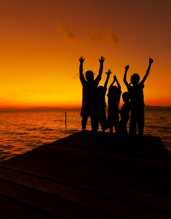 Silhouette of children at sunset photo