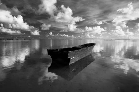 black an white: Barco solo con la reflexi�n de las nubes y el cielo tomadas en Borneo, Sabah, Malasia