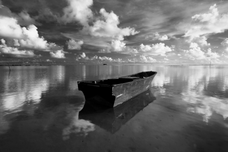 black and white: Lonely boat with reflection of clouds and sky taken at Borneo, Sabah, Malaysia
