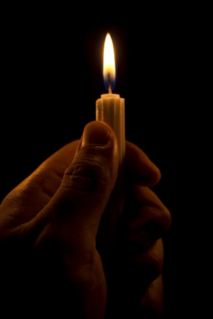 prayer candles: Hand holding a candle in the dark