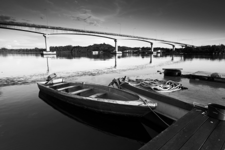 Tied boat on a jetty in black and white photo