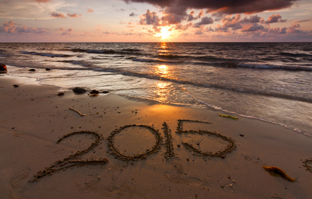 Year 2015 written on sand at sunset photo
