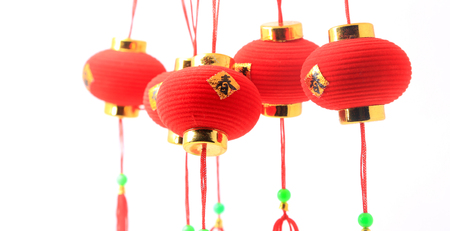 Small red Chinese lanterns hanging over white background.  The Chinese word means fortune.