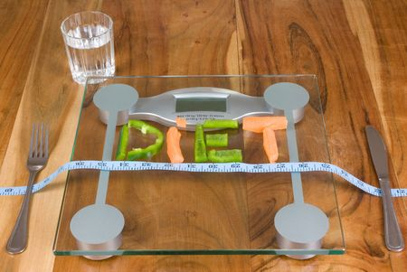 diet spelled out on scales with tape mesure ,knife , fork  and glass of water Stock Photo - 4176706