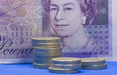 sterlina: libras monete con venti libra nota come sfondo blu, con le conoscenze acquisite Archivio Fotografico