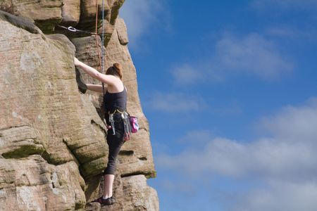 female rock climber climbing cliff face photo