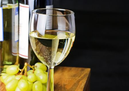 discreto: vino blanco con fondo negro de uvas  Foto de archivo