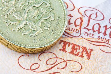 earn money: pound coin on a ten pound  note Stock Photo