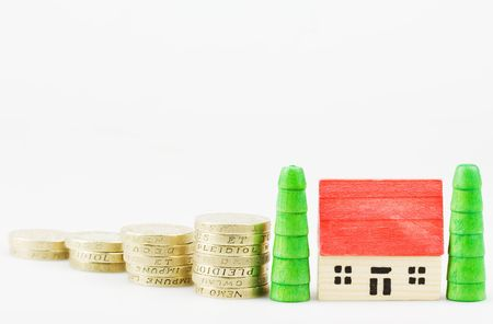 concep: coins with a wooden house mortgage concep