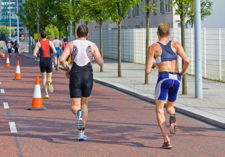 men racing in the running section of a triathlon  photo