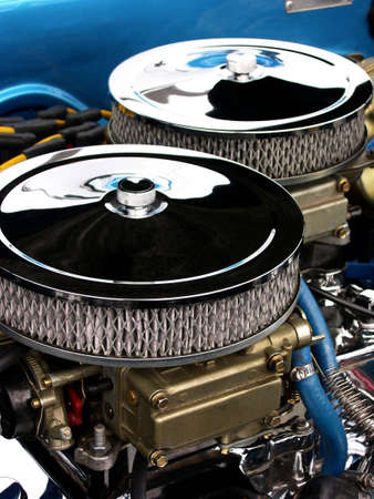 atop:  A clean engine compartment consisting of two chrome air filters sitting atop two carburetors. Stock Photo