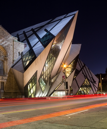 the place of interest: Toronto, Canada - October 16, 2013  The Royal Ontario Museum in Toronto at night with the trails from cars going past Editorial