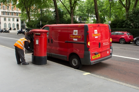 mail man: London, UK - June 22, 2013  Royal Mail man collecting the mail from a post box in London