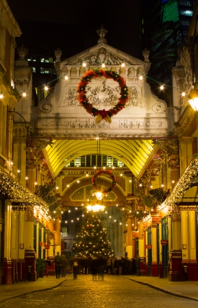 London, UK - December 6, 2013  One of the entrances towards Leadenhall Market at Christmas during the evening  Around the Christmas tree people can be seen socialising