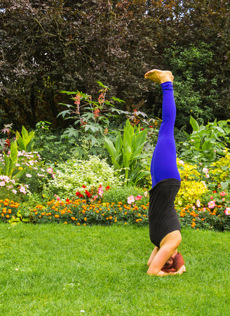 headstand: A lady doing a Yoga Headstand outside in a park Stock Photo