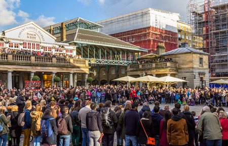 covent garden market: LONDON, UK - 1ST MARCH 2014  The Front of Covent Garden Market showing people gathering around watching an entertainer