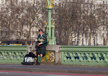 bagpipes: LONDON, UK - 9TH MARCH 2014  Man playing the bagpipes on Westminster Bridge in London