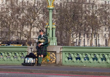gaita: LONDRES, Reino Unido - 9 DE 03 2014 Hombre tocando la gaita en el puente de Westminster en Londres