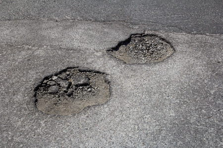 pot hole: High view of pot holes in a road during the day Stock Photo