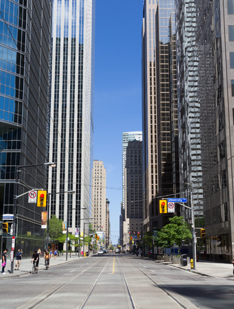 king street: TORONTO, CANADA - JUNE 1ST, 2014: A view down part of King Street West in Toronto showing buildings Street Car lines and people on the street
