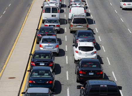 gridlock: TORONTO, CANADA - JUNE 6 2014: Queue of Traffic on a road in central Toronto during the day