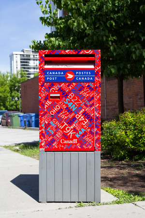postes: TORONTO, CANADA - JUNE 6 2014: Front of a colorful Canada Post box during the day Editorial
