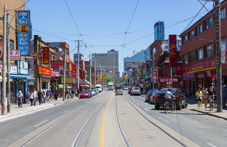 TORONTO, CANADA - JUNE 7 2014  A view down Spadina Avenue in Central Toronto during the day  People and traffic can be seen on the street